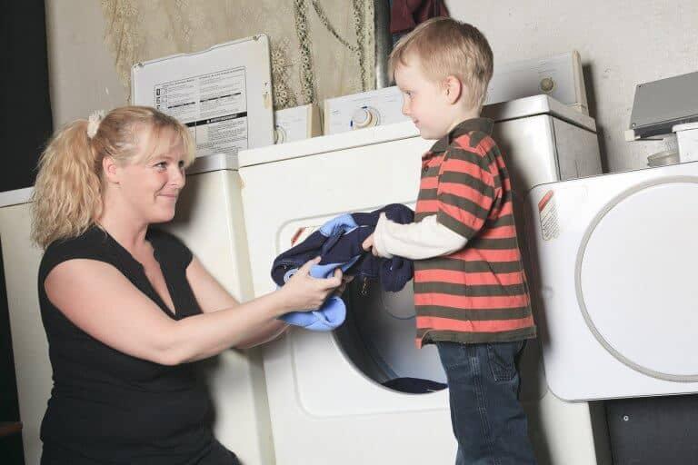 Kind helpt moeder met de was doen