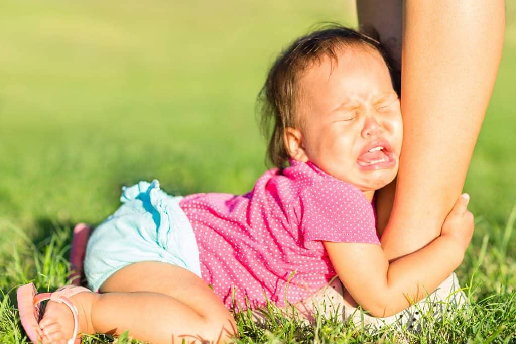 Peuter huilt en pakt enkels van de moeder vast