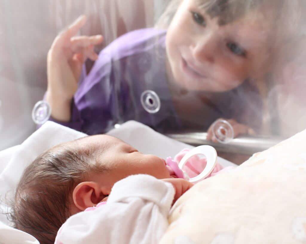 Kindje kijkt naar pasgeboren baby