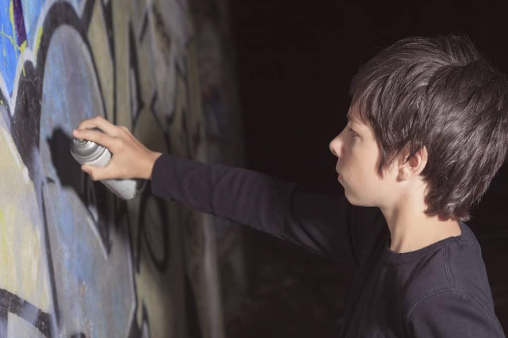 Jongen maakt graffiti