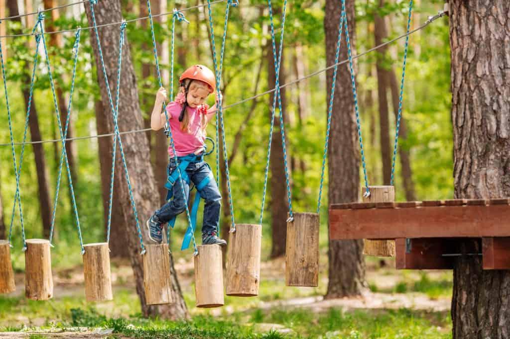 Meisje loopt over houtblokken in klimbos