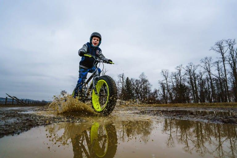 Jongen fiets door modderplassen