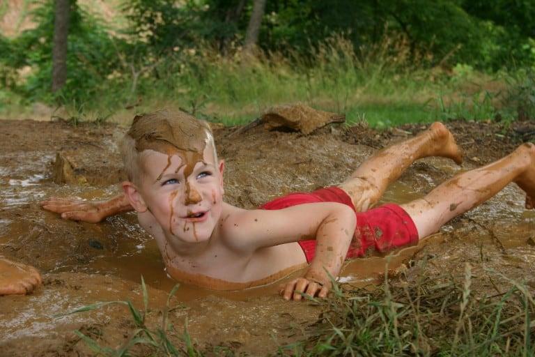 Jongen glijdt door de modder