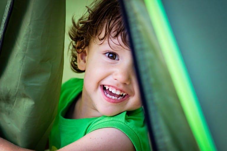 Kind kijkt uit tent