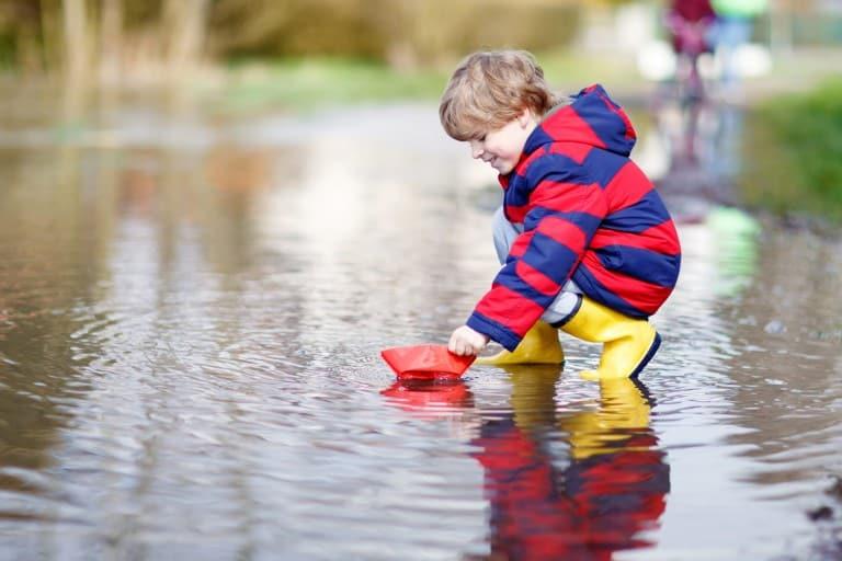 Kind speelt met boot in een plas water