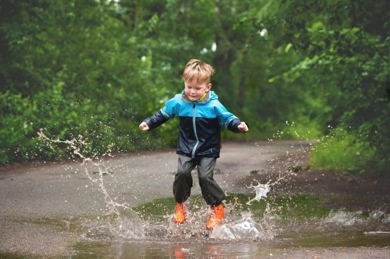 Kind stampt in de regenplas