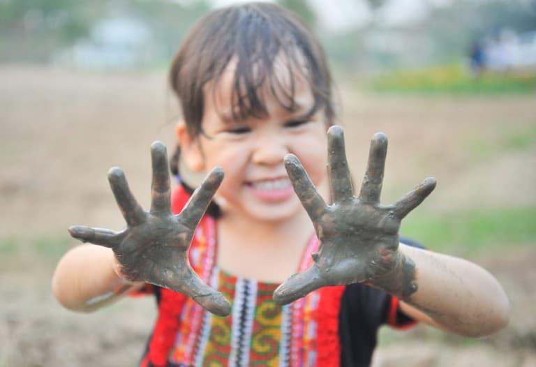 Kinderhanden met modder