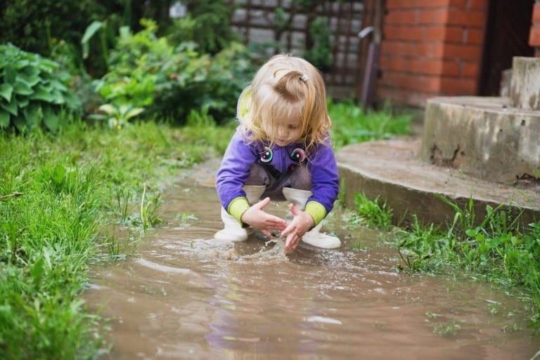 Meisje met handen in een plas water