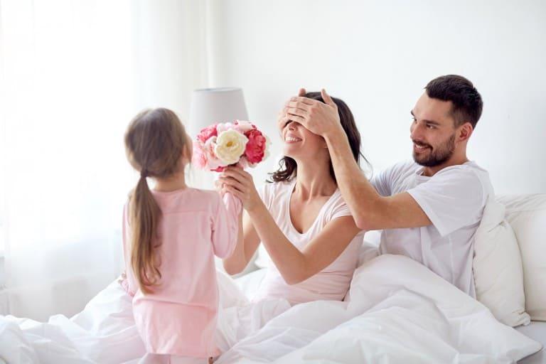 Kind geeft bloemen aan mama