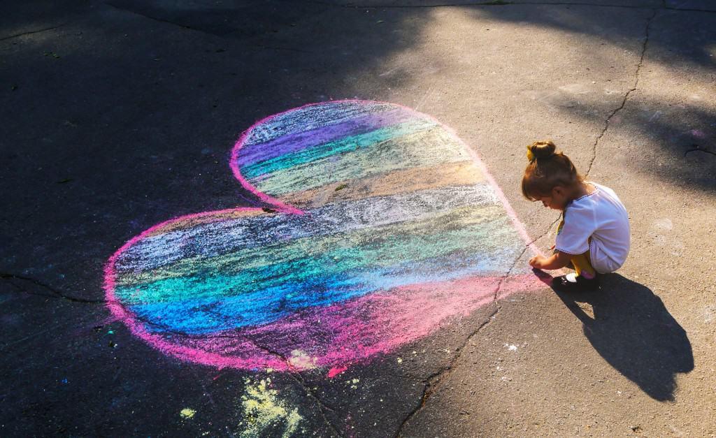 Kind maakt stoepkrijt tekening