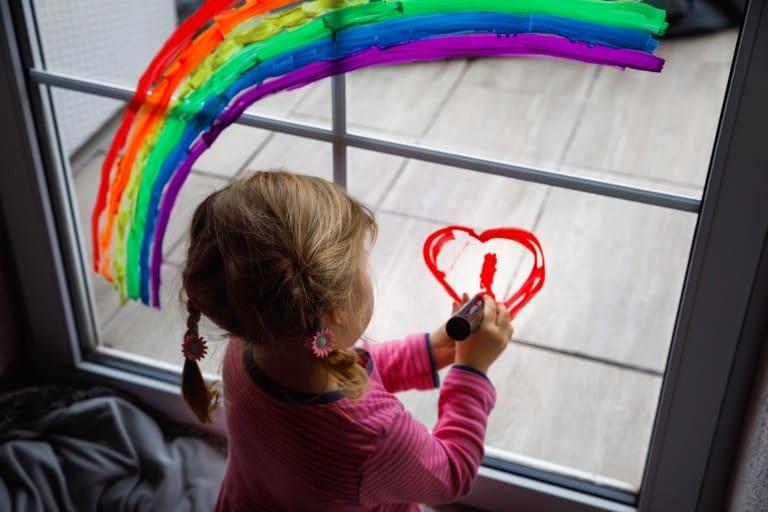 Kind maakt tekening op raam